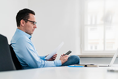 Businessman holding document while using smart phone at office - p300m2274102 by Daniel Ingold