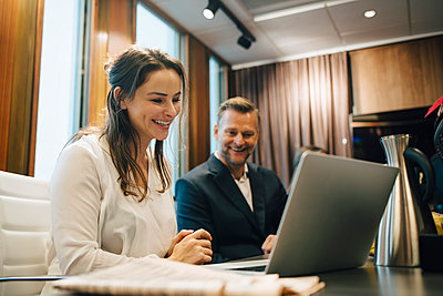 Smiling male and female lawyer discussing over laptop in office - p426m2270840 by Maskot