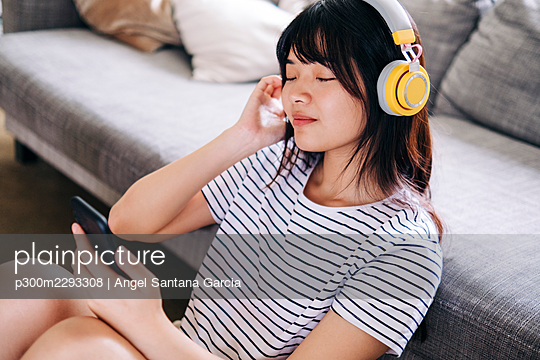 Woman with mobile phone listening music through headphones in living room - p300m2293308 by Angel Santana Garcia