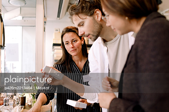Saleswoman showing perfume box to couple at fashion store - p426m2213464 by Maskot