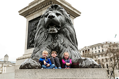 Three Smiling Siblings Sit on the Trafalgar Square Lion - p1166m2094736 by Cavan Images