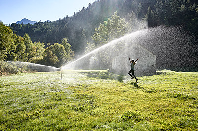 Woman jumping on grass near sprinkler during sunny day - p300m2226758 by Veam