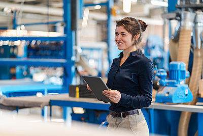 Smiling businesswoman using digital tablet while standing at industry - p300m2250867 by Daniel Ingold