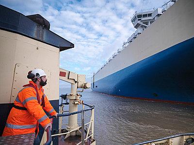 Worker standing on deck of tugboat - p429m747055f by Monty Rakusen
