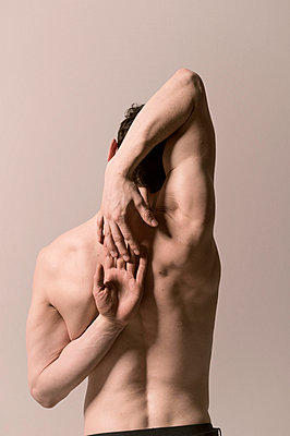 Rear view of young man practicing yoga - p947m2163941 by Cristopher Civitillo
