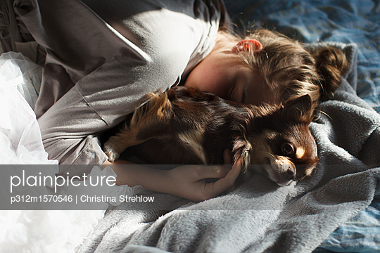 Teenage girl sleeping with dog - p312m1570546 by Christina Strehlow