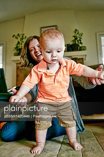 Caucasian mother helping baby walk on living room floor - p555m1420446 by Peathegee Inc