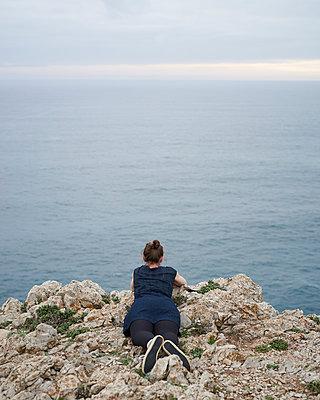 Frau liegt auf Klippe am Meer - p1124m1112568 von Willing-Holtz