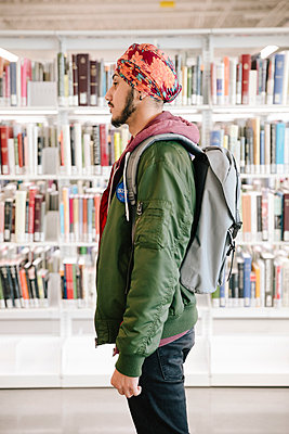 Portrait of student in university library with backpack - p1192m2110223 by Hero Images