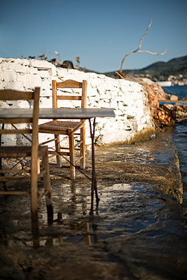 Two rustic chairs and table in a Greek waterside taverna, nearly standing in the water. - p1433m1526041 by Wolf Kettler