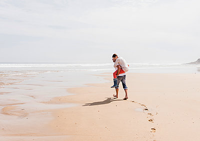 Mature man carrying wife piggyback on the beach - p300m1189037 by Uwe Umstätter