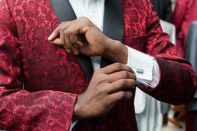 Close-up of a man wearing tuxedo in tailor shop adjusting the sleeves - p300m1568229 von Authentic Images