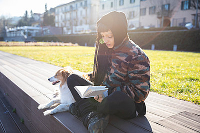 Young woman with piercings and braids sitting with her dog on a bench reading a book, Como, Italy - p300m2166816 by 27exp