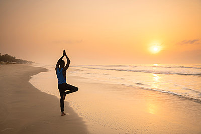 Man practising yoga on beach - p429m2091810 by Ben Pipe Photography