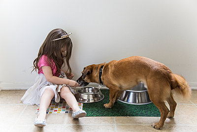 Caucasian girl feeding dog on floor - p555m1311493 by Andie Mills