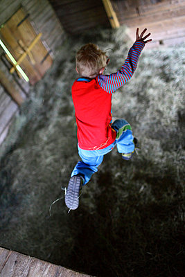 Child jumping on hay in barn - p575m744087f by Fredrik Ludvigsson