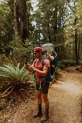 Father with baby exploring forest, Queenstown, Canterbury, New Zealand - p924m2098222 by Peter Amend