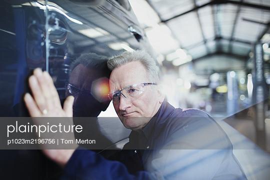 Focused male mechanic examining car in auto repair shop - p1023m2196756 by Tom Merton