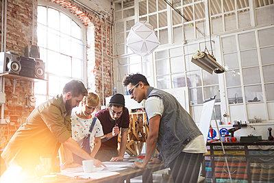 Designers meeting, reviewing plans in workshop - p1023m1486406 by Agnieszka Olek