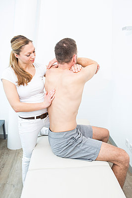 Physiotherapist helping to do exercises - p1026m1025116f by Patrick Frost
