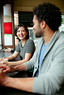 Happy woman talking to man in cafe - p1166m1163688 by Cavan Images