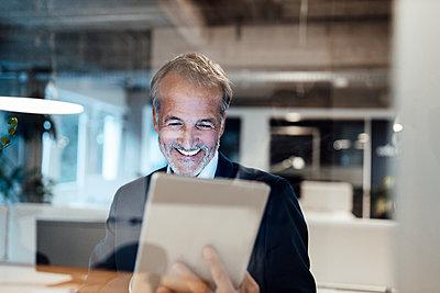 Senior male entrepreneur using digital tablet in office - p300m2287697 by Gustafsson