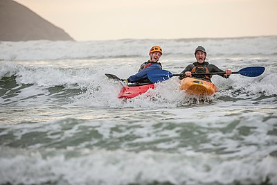Two men sea kayaking - p429m1021909f by Colin Hawkins