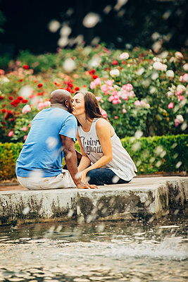 Couple kissing at fountain in garden - p555m1306233 by Inti St Clair photography