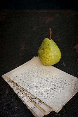 Eine Birne auf einem Stapel alter Briefe - p946m951094 von Maren Becker