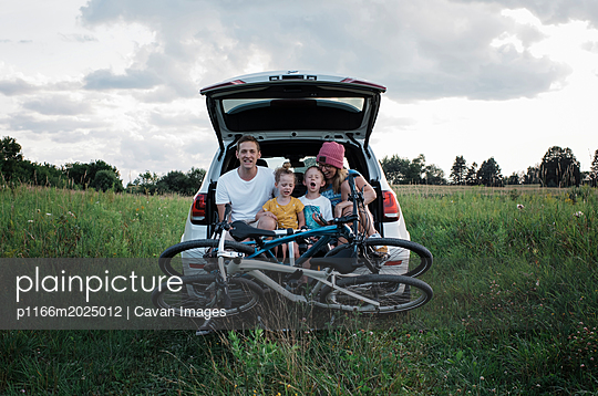 Happy family with bicycles sitting on car trunk amidst grassy field against cloudy sky - p1166m2025012 by Cavan Images
