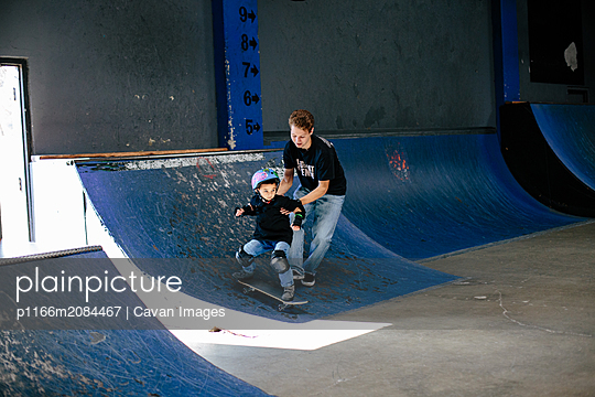 Skateboard instructor helps student skate down a ramp - p1166m2084467 by Cavan Images