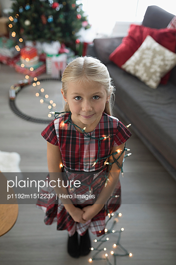 Portrait cute girl wrapped in Christmas tree string lights in living room - p1192m1512237 by Hero Images