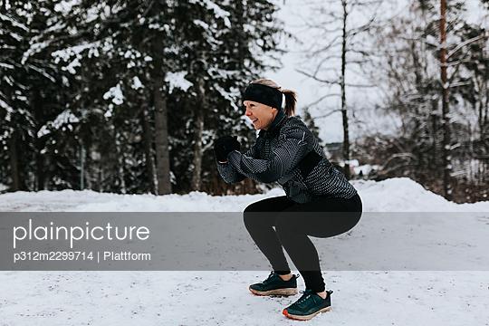 Woman exercising at winter - p312m2299714 by Plattform