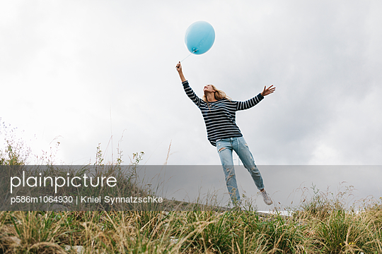 Young woman with balloon outdoors - p586m1064930 by Kniel Synnatzschke