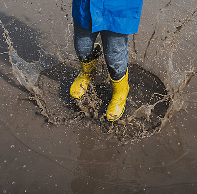 Low section of playful boy wearing rubber boots while splashing puddle - p1166m2011825 by Cavan Images