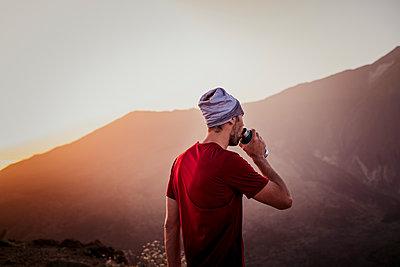 Hiker drinking water at sunset in Guajara mountain, El Teide - p1166m2131192 by Cavan Images