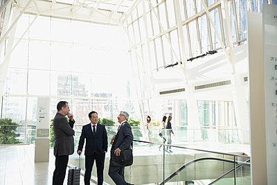 Businessmen talking in airport atrium - p1192m1231130 by Hero Images