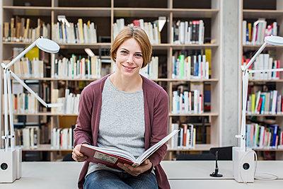 Studentin blättert in einem Buch in der Bibliothek - p1284m1452029 von Ritzmann