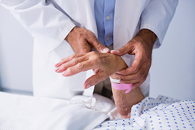 Doctor examining patients pulse - p1315m1227960 by Wavebreak