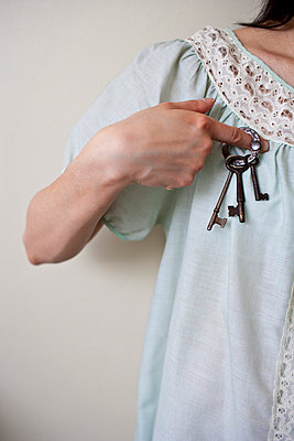 Woman holds a set of old keys against her chest - p5350327 by Michelle Gibson