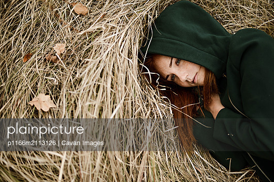 Close-up portrait of teenage girl with red head lying on grassy - p1166m2113126 by Cavan Images