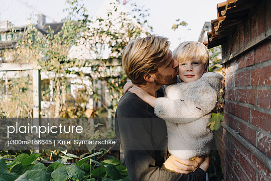 Father holding and kissing son in garden - p300m2166645 by Kniel Synnatzschke