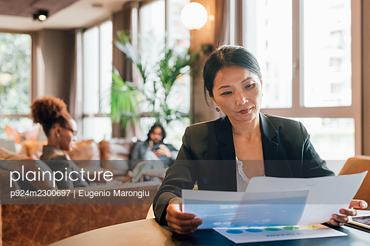 Italy, Businesswoman looking at documents at table in creative studio - p924m2300697 by Eugenio Marongiu