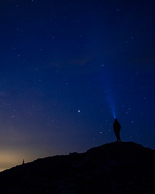 A man stares up at the night sky with a headlamp. - p1166m2136733 by Cavan Images
