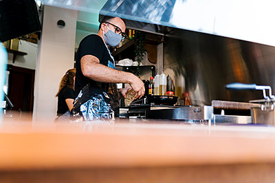 Male barista wearing protective face mask while cooking in kitchen of coffee bar during COVID-19 - p300m2220707 by Ezequiel Giménez