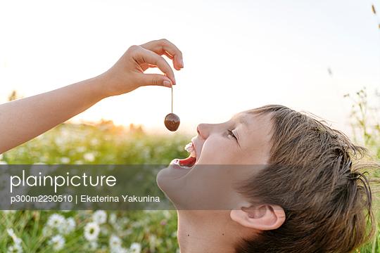 Girl feeding cherry to boy at field - p300m2290510 by Ekaterina Yakunina