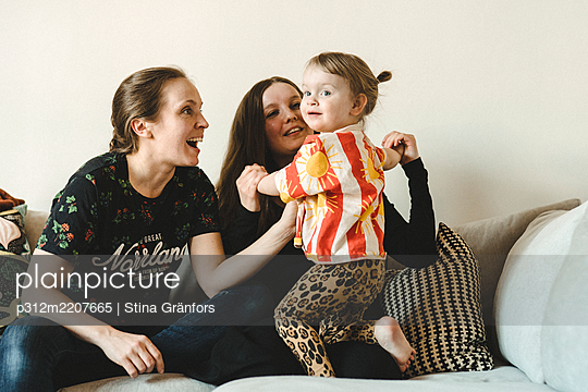 Girl with mothers on sofa - p312m2207665 by Stina Gränfors