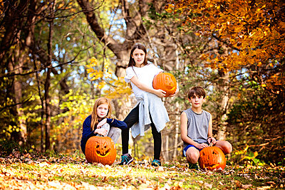 Three Children With Carved Pumpkins Outdoors - p1166m2147162 by Cavan Images