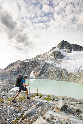 Backpacker hiking with view of lake and mountains - p1166m2162476 by Cavan Images