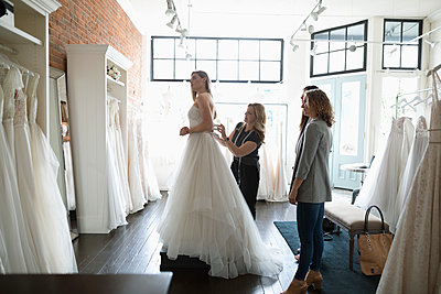 Bride and friends at wedding dress fitting in bridal boutique - p1192m1583299 by Hero Images